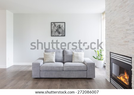 Bright and clean interior design of a luxury living room with hardwood floors, fireplace and sofa.  - stock photo