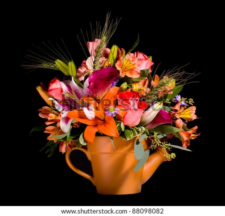 Bright and colorful bunch of flowers arranged in a watering can plant pot and isolated against black - stock photo