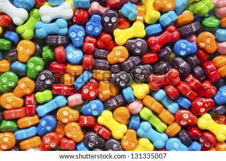 Bright and colorful skull and bone shaped candies in a gumball dispenser. - stock photo