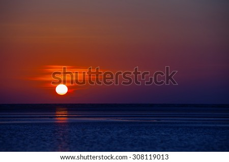Bright ball of the sun, burning through the haze of the late afternoon sky, dipping toward the horizon over the tropical sea at sunset. - stock photo