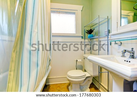 Bright bathroom with window. Green and white  wall matches with striped green curtains. - stock photo