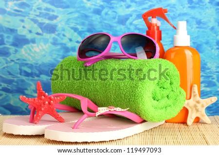bright beach accessories, on blue sea background - stock photo