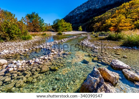 Bright Beautiful Fall Foliage on the Banks of the Rocky Crystal Clear Frio River. - stock photo