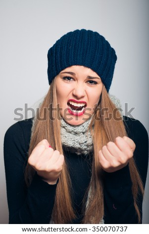 bright beautiful girl angry shouts, studio photo isolated on a gray background - stock photo