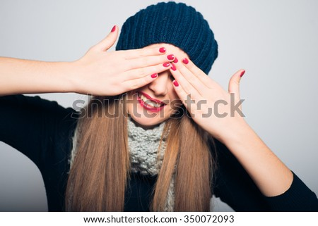 bright beautiful girl closes eyes with her hands, Christmas and New Year concept, studio photo isolated on a gray background - stock photo