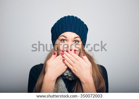 bright beautiful girl covers her mouth with her hands and is silent, Christmas and New Year concept, studio photo isolated on a gray background - stock photo