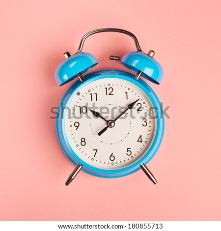 Bright blue alarm clock lying on pink surface - stock photo