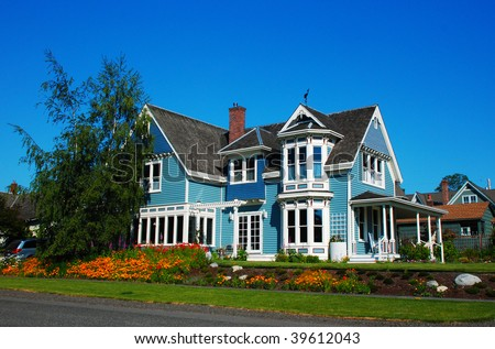 Bright blue house in sunlght with colorful poppies and some graceful trees - stock photo