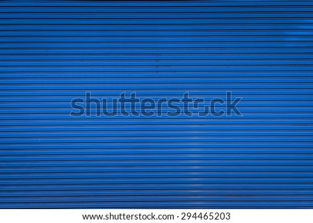 Bright blue metal sliding door with key hole, taken on a cloudy day. - stock photo
