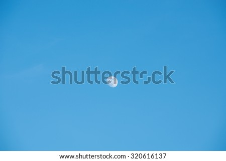 Bright blue morning sky with the half moon - stock photo