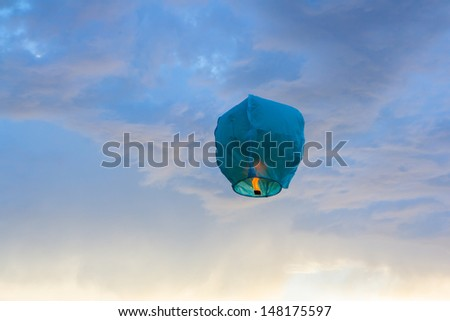 Bright blue paper Lantern flying in the sky - stock photo