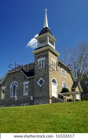 Bright blue skies frame Forks of Ivy Baptist Church in North Carolina.  Aging church has old stone walls and white wooden trim including bell tower and steeple. - stock photo