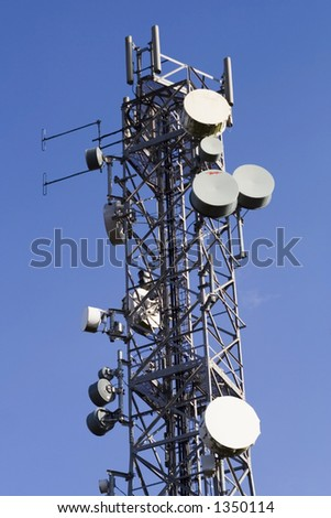 Bright blue sky and cell phone transmitter tower. - stock photo