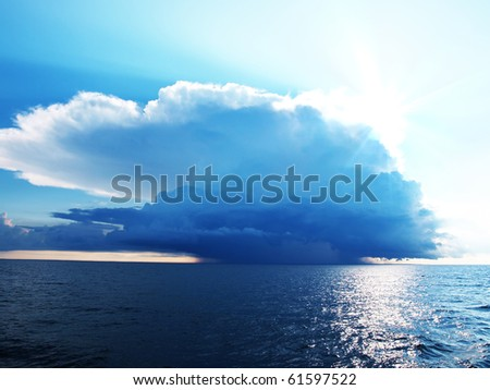 Bright blue sky with stormy clouds over a calm sea - stock photo