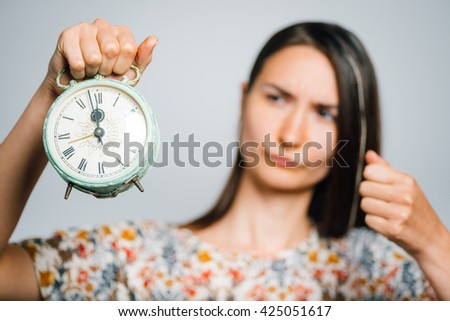 bright brunette girl breaks alarm clock isolated on a gray background - stock photo