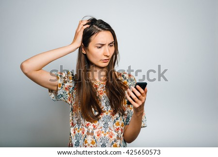 bright brunette girl looks confusion on the phone isolated on a gray background - stock photo