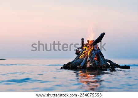 Bright campfire on the sea surface - stock photo