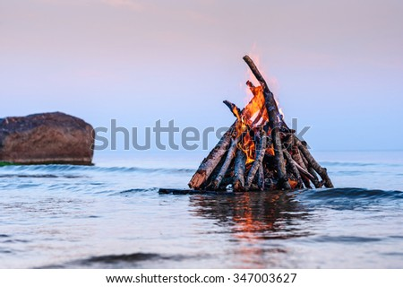 Bright campfire on the sea surface at sunset  - stock photo