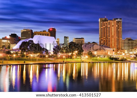 Bright city lights reflecting in still Torrens river waters of Adelaide, capital of South Australia. City architecture illuminated before sunrise. - stock photo