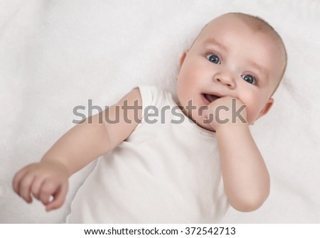 Bright closeup portrait of adorable baby.Funny laughing baby lying on back and looking at camera. - stock photo