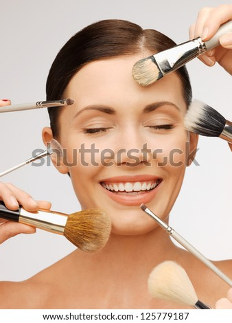 bright closeup portrait picture of beautiful woman with brushes. - stock photo