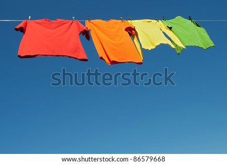Bright clothes on a laundry line and blue sky with copy space. - stock photo