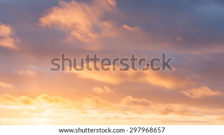 Bright cloudscape background with colors from golden through to blue. - stock photo