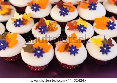 Bright colored fall themed cupcakes and a cake at a wedding celebration - stock photo