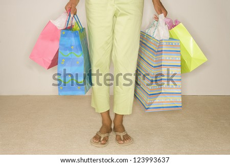 Bright colored shopping bags held by handles by mixed cultural woman in flip flops and green pants 3/4 length - stock photo