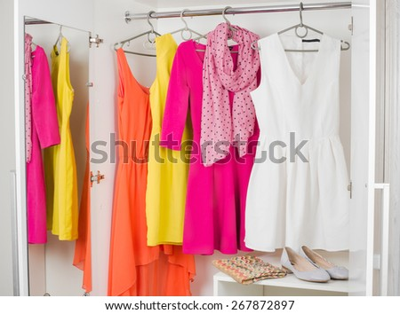 bright colorful female dresses hanging on coat hanger, pink scarf, shoes and handbag in white wardrobe - stock photo