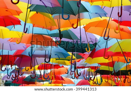 Bright colorful hundreds of umbrellas floating above the street - stock photo