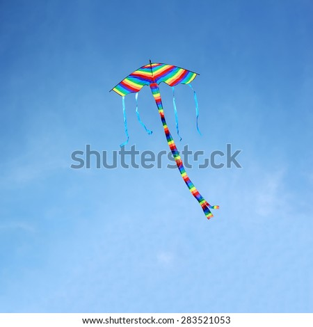 Bright colorful kite flying in the blue sky. - stock photo