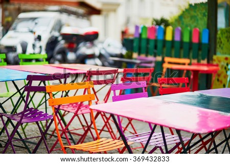 Bright colorful tables of an empty Parisian outdoor cafe on Montmartre - stock photo