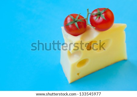 Bright colorful tasty and delicious still life made of two red ripe fresh cherry tomatoes with stems on top of a piece of cheese with big internal holes against blue background. Copy space - stock photo