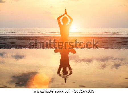 Bright colors: Yoga woman sitting in lotus pose on the beach during sunset, with reflection in water. - stock photo