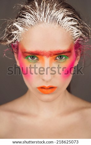 bright, contrasting portrait of a beautiful young girl with a scattering of pigment color on the face, with colored lashes, colored hair, glossy skin, bright make-up, red, green on a dark background - stock photo