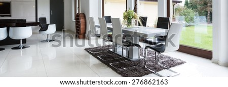 Bright dining room connected with kitchen in modern residence - stock photo