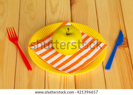 Bright disposable tableware, napkin and apple on a background of light wood. View from above. - stock photo