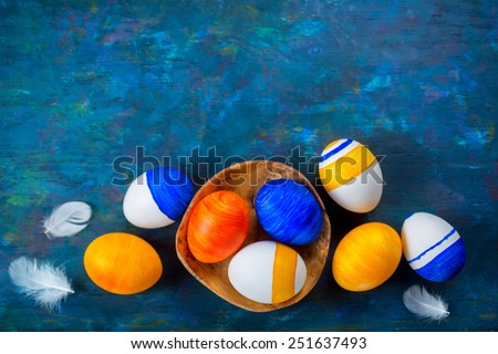 Bright Easter eggs on a blue background - stock photo
