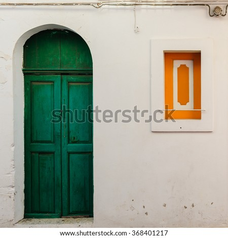 Bright emerald old door and window of a typical house on Stromboli island, Sicily, Italy. - stock photo