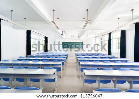 Bright empty classroom with desks and chairs - stock photo