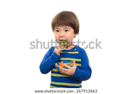Bright eyed three year old boy eating broccoli and carrots on, isolated on a white background. Little child eating healthy food and vegetables, holding a blue bowl of snacks. Happy and healthy living. - stock photo
