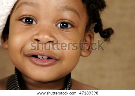 bright eyed toddler with white head wear and men's tie - stock photo
