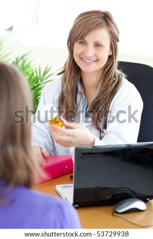 Bright female doctor holding medicine in her office - stock photo