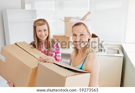Bright female friends holding boxes after moving - stock photo