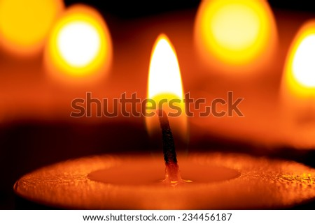 Bright flame of candle in darkness - stock photo