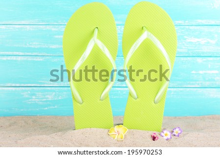 Bright flip-flops on sand, on wooden background - stock photo