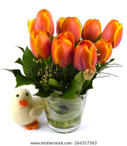 Bright flowering spring tulips in red orange and yellow on a vase and a easter decoration - stock photo