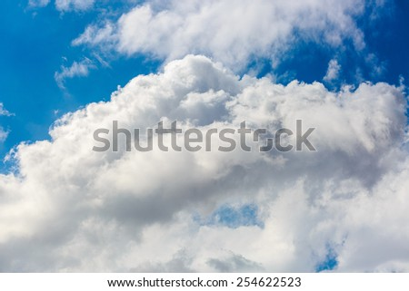 Bright fluffy clouds in blue sky - stock photo
