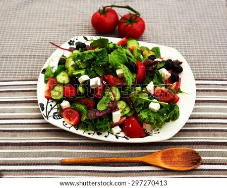 Bright fresh summer salad with cherry tomatoes, arugula, and a mix of various herbs, feta cheese is cut into small pieces, the salad served on big white plate - stock photo
